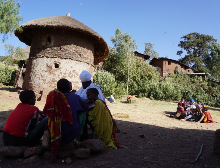 Teachings with traditional house in background
