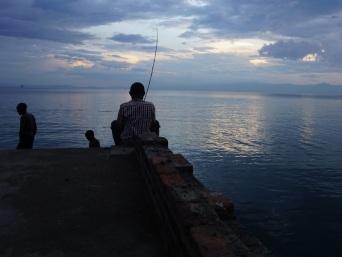 A boy fishing at sunset